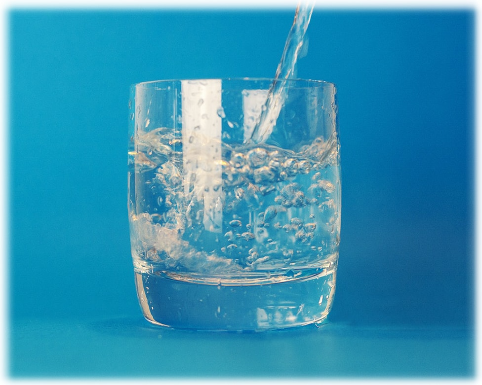 A glass of water been filled against a blue background