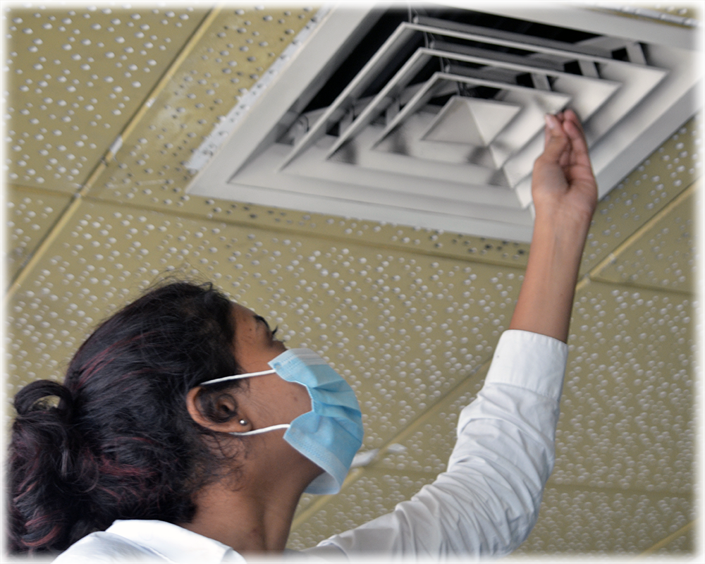 Individual wearing a mask attempting at removing a vent on ceiling